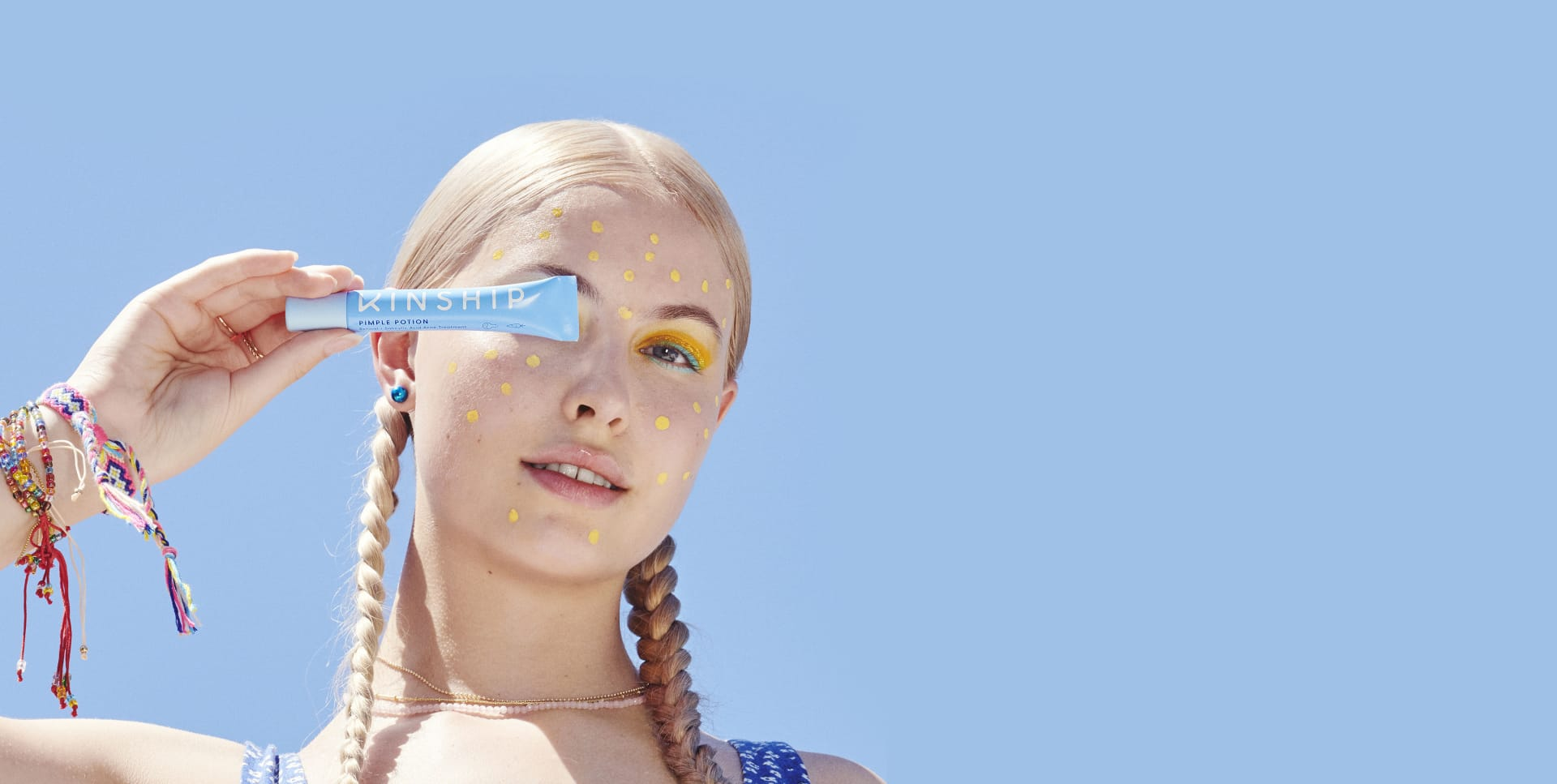 A young woman holds the Pimple Potion tube with the yellow acne treatment dotted on her face | Kinship