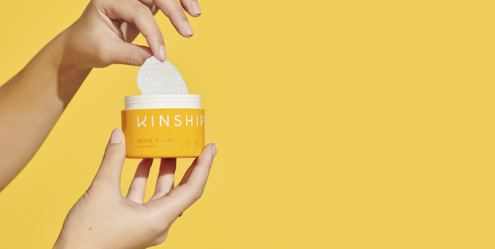 Hands holding Insta Swipe Exfoliating Pads | Kinship