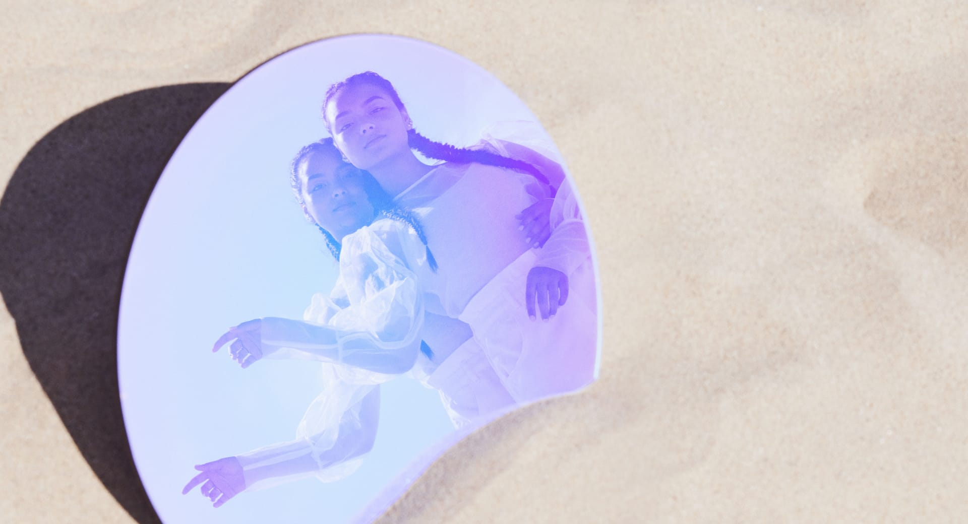 Prismatic reflection of twin sisters from a mirror in the sand | Kinship