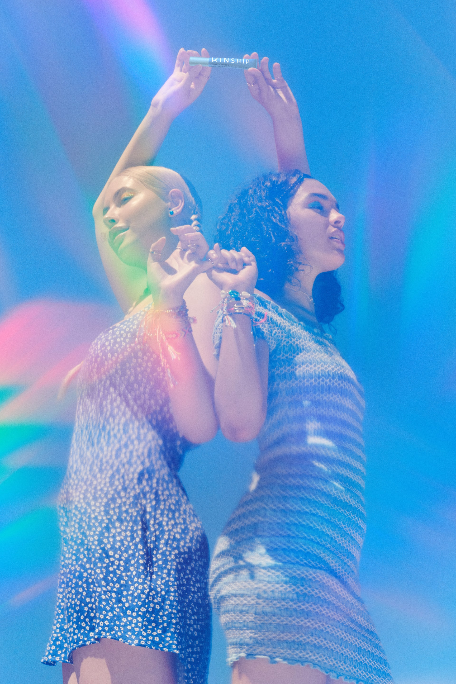 Two friends hold hands outdoors, cast in a rainbow prism of light | Kinship