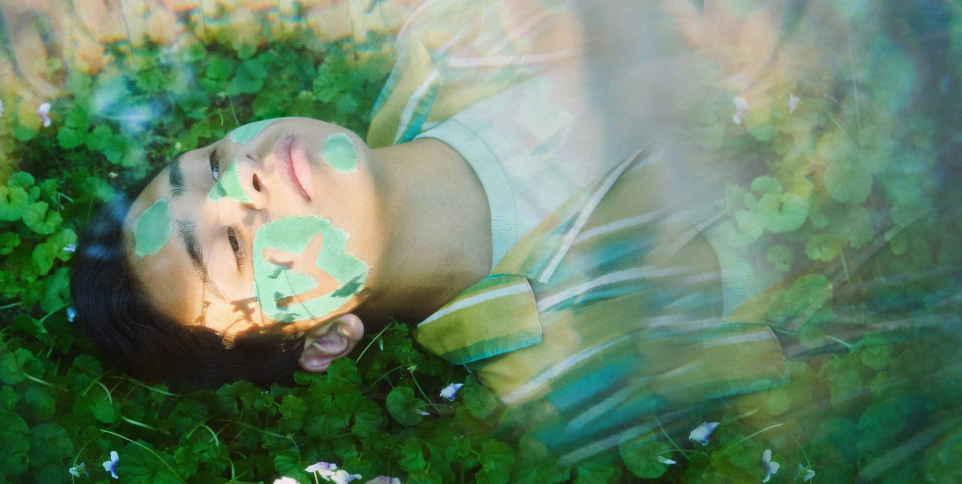 Young man lays in a green field wearing Mint Mud mask | Kinship