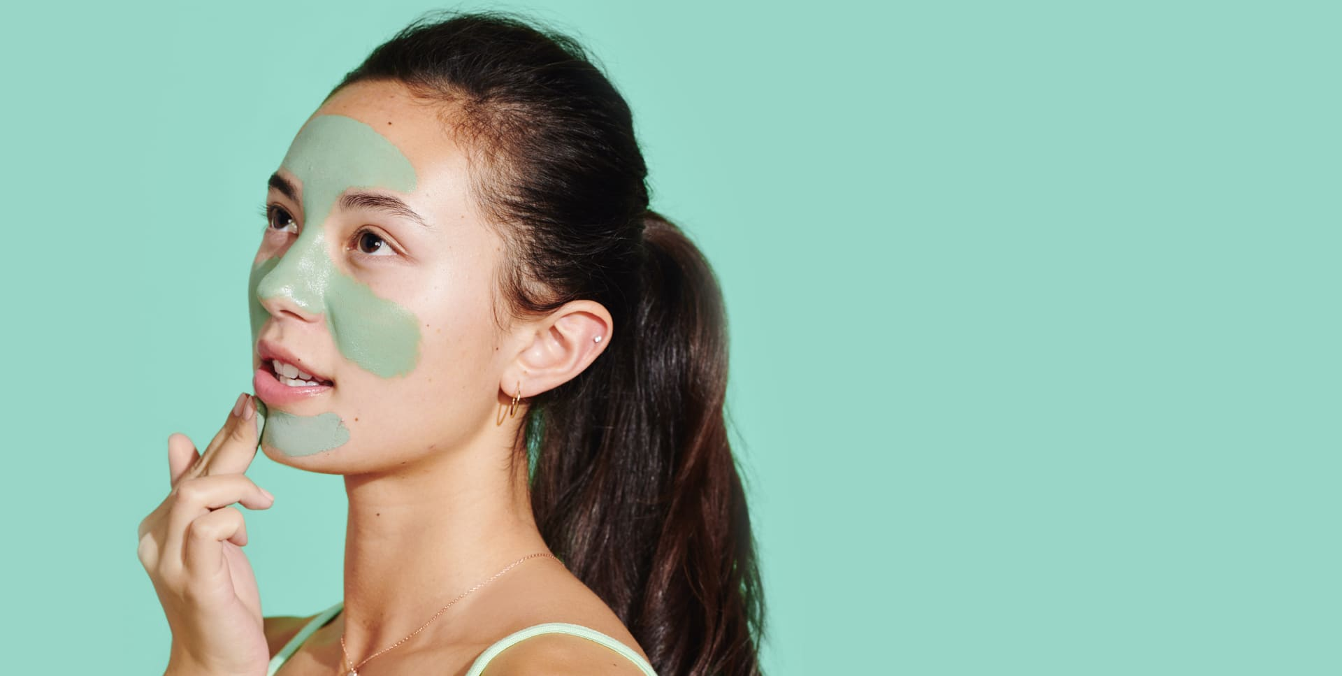 Young woman applies Mint Mud detox mask to her face with her fingers
