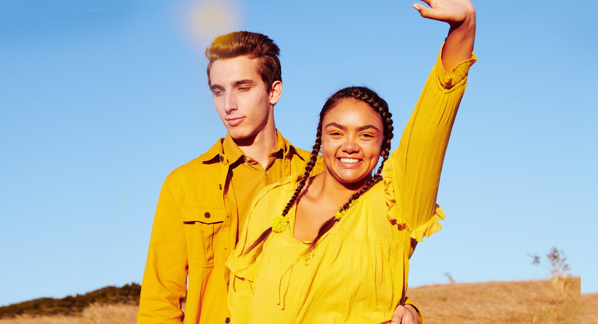 Smiling couple in yellow outfits stand on a California hillside | Kinship