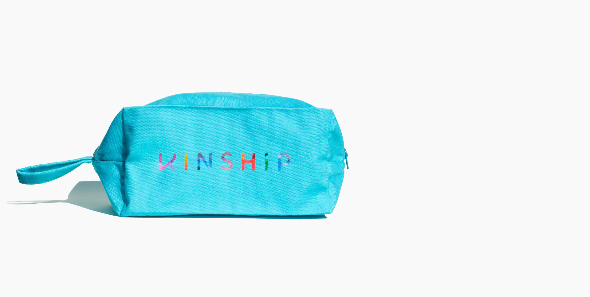 Sky blue dopp kit with Kinship multi-color logo, front facing