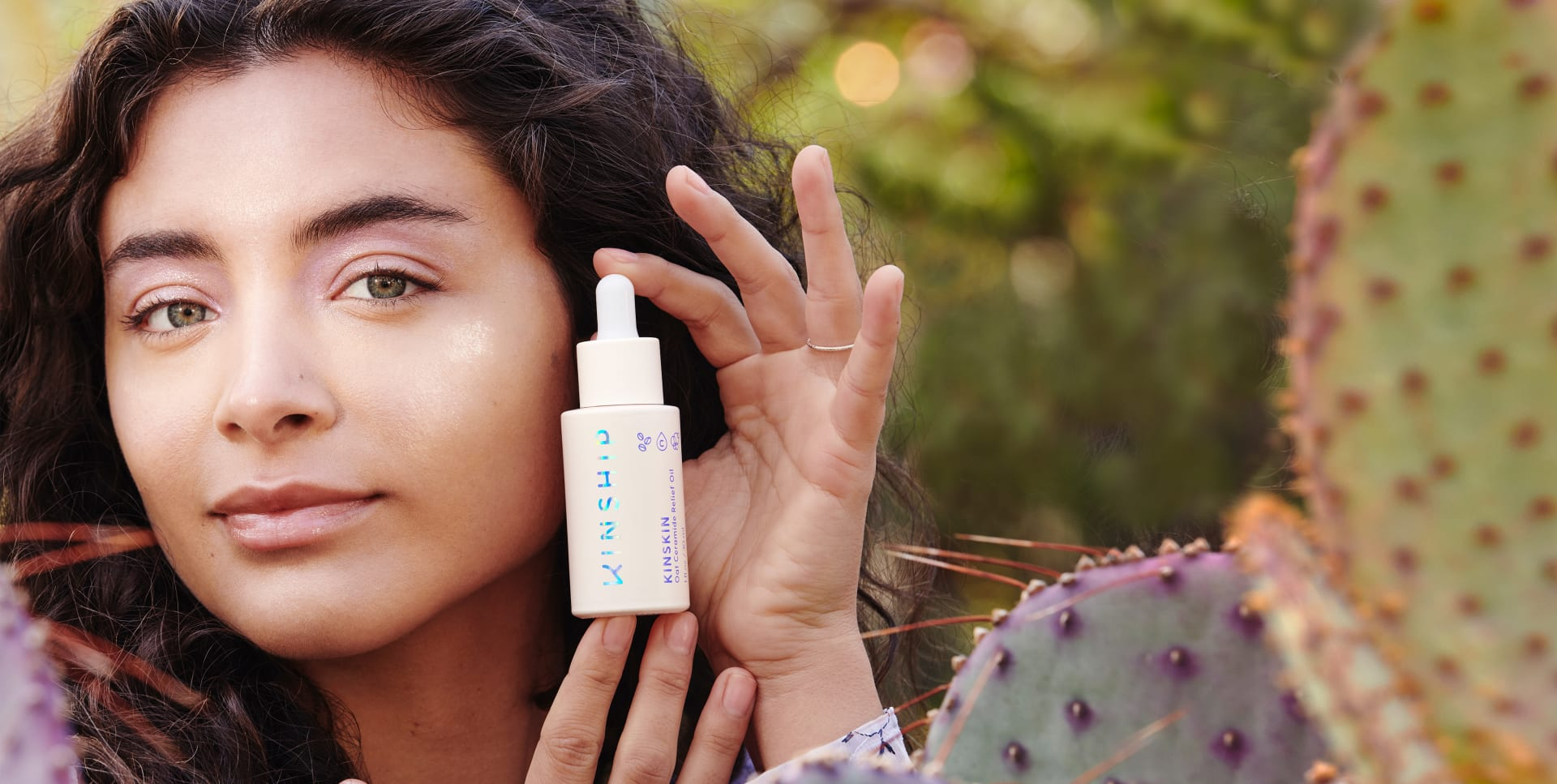 Adriana, standing in a prickly pear cactus garden, holds Kinskin Oat Ceramide Face Oil bottle up next to their cheek