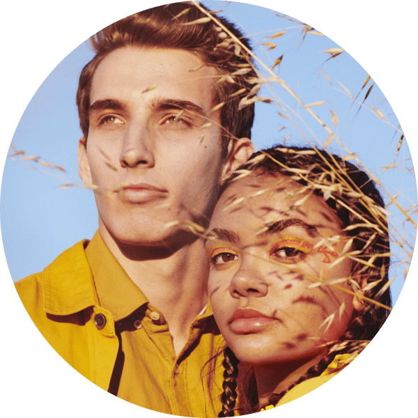 Man and woman wearing yellow stand in a field | Kinship