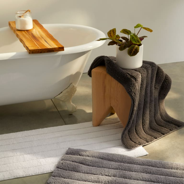 Dark gray and white tufted bath rugs draped over a stool and on the floor near a bathtub