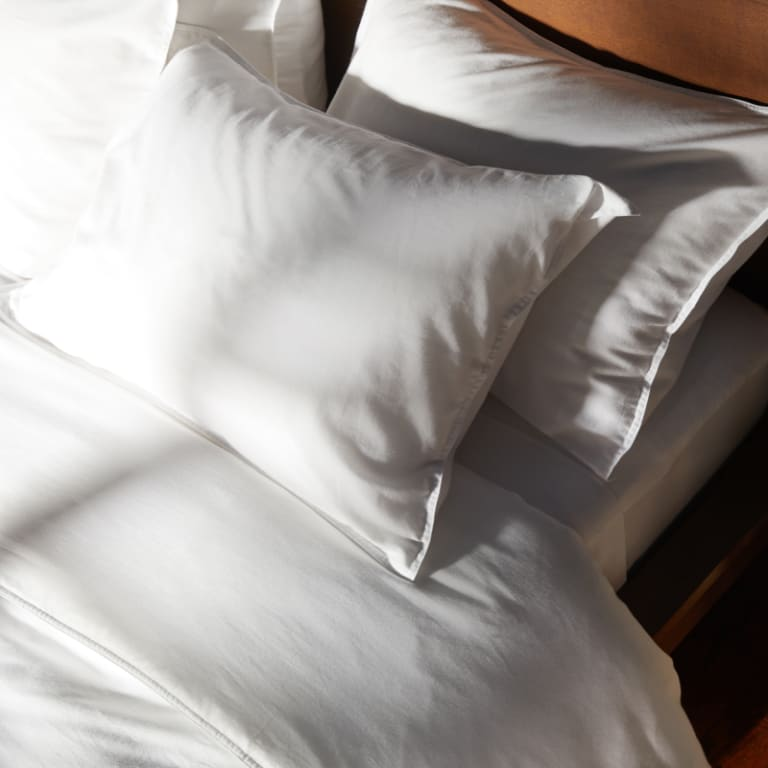 White Heathered Cashmere sheets on a sun-drenched bed