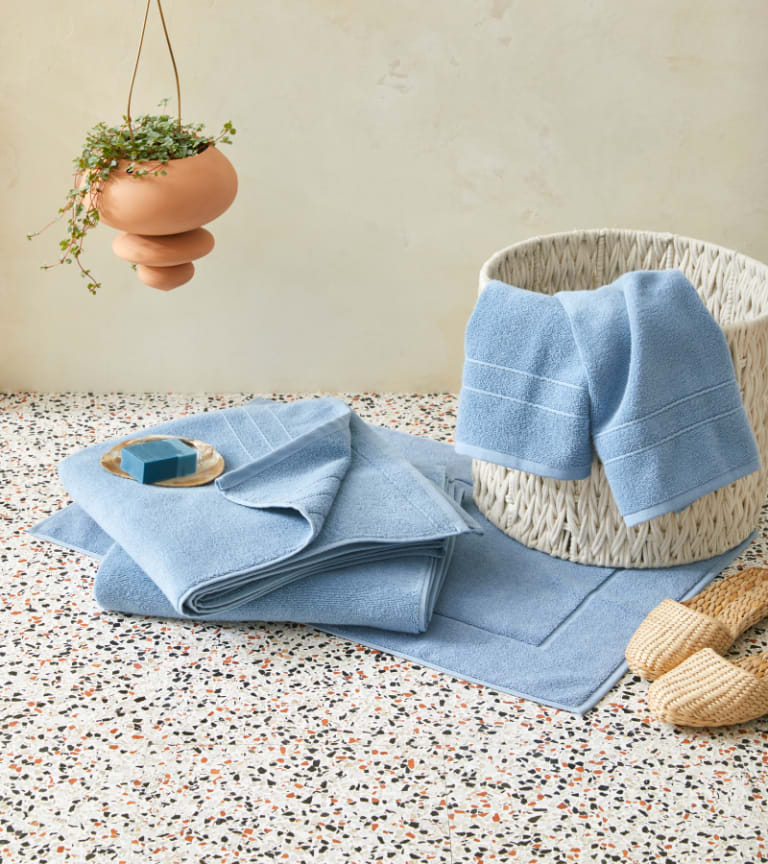 Ocean blue bath towels folded on the floor and draped over a rattan basket with rattan slippers, a hanging plant, and a tray with soap nearby
