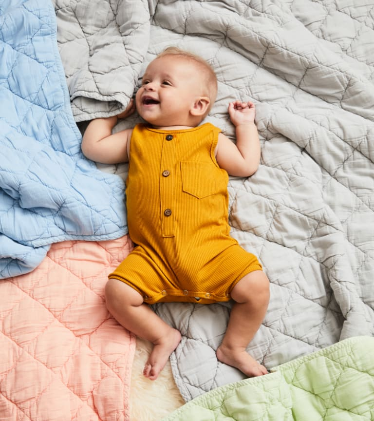 Smiling baby laying on blue, gray, green, and pink quilts