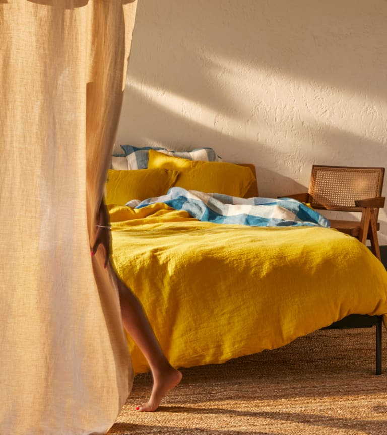 Cozy bed styled with our latest Fall Linen sheet collection in Ochre and Ink Blue Gingham.