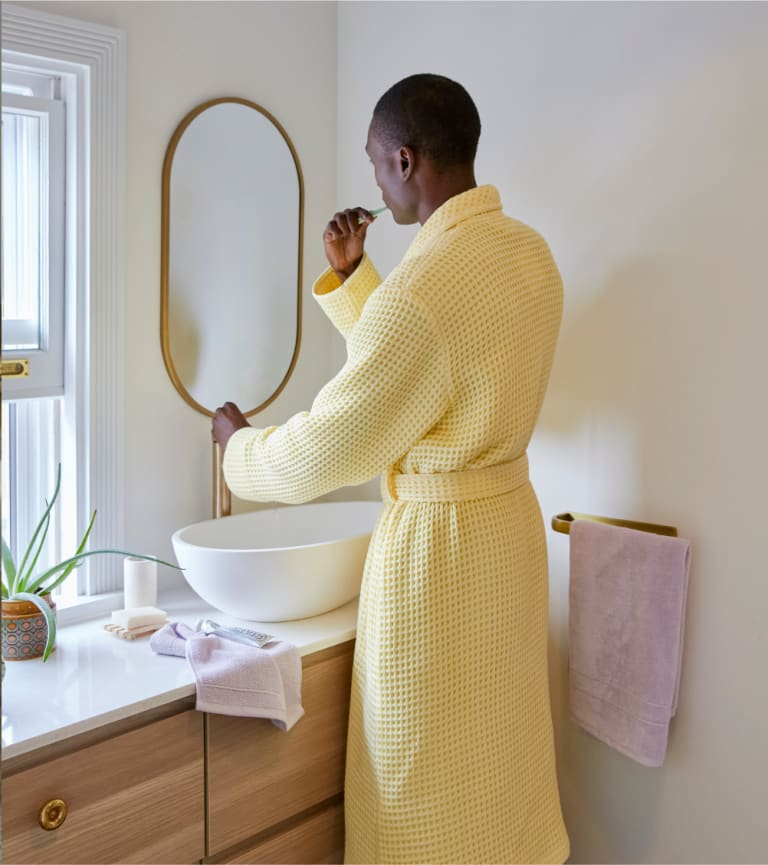 Man brushing his teeth in our new Popcorn Waffle Robe.