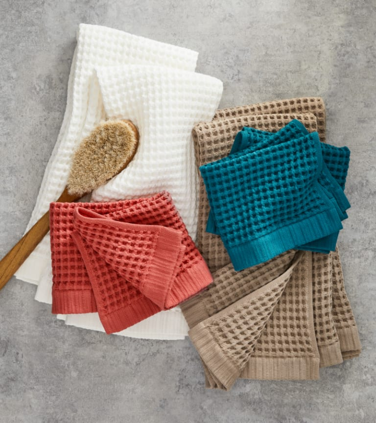 Bathroom counter featuring new colors of our Waffle Washcloths and Hand Towels: Cream, Red Clay, Ink Blue, and Dark Caramel.