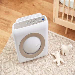 Coway Airmega AP-1512HH White on a bedroom floor next to a baby's crib.