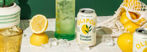 Photo of a Ginger lemon can glistening amongst a bag of spilled lemons and frothy cups.