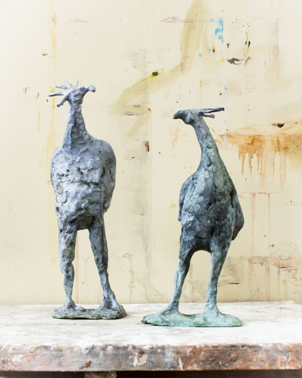 two bronze sculptures of birds with long legs