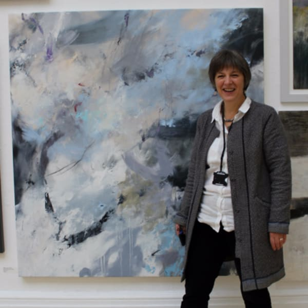Alison Bevan in front of a large seascape painting