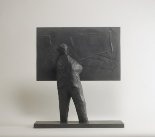bronze sculpture of a man looking at a picture
