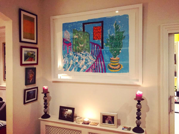 interior photo of brightly coloured prints on wall