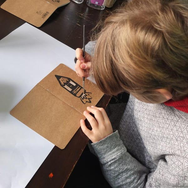 a young boy adds paint to a lino cut print