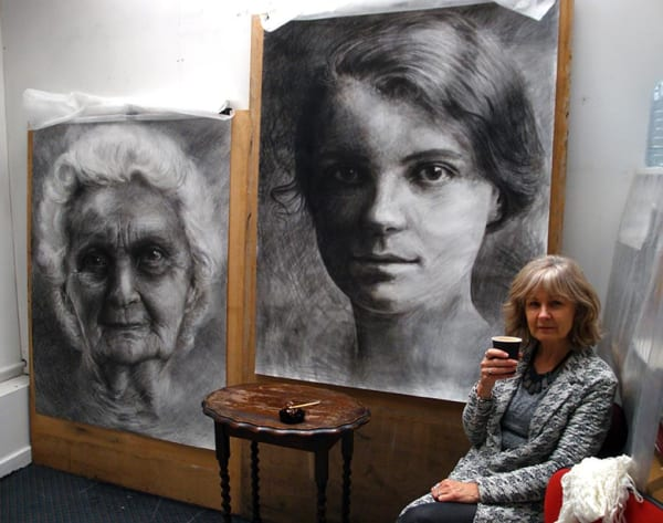 artist Ruth Wallace in her studio with artworks on the wall