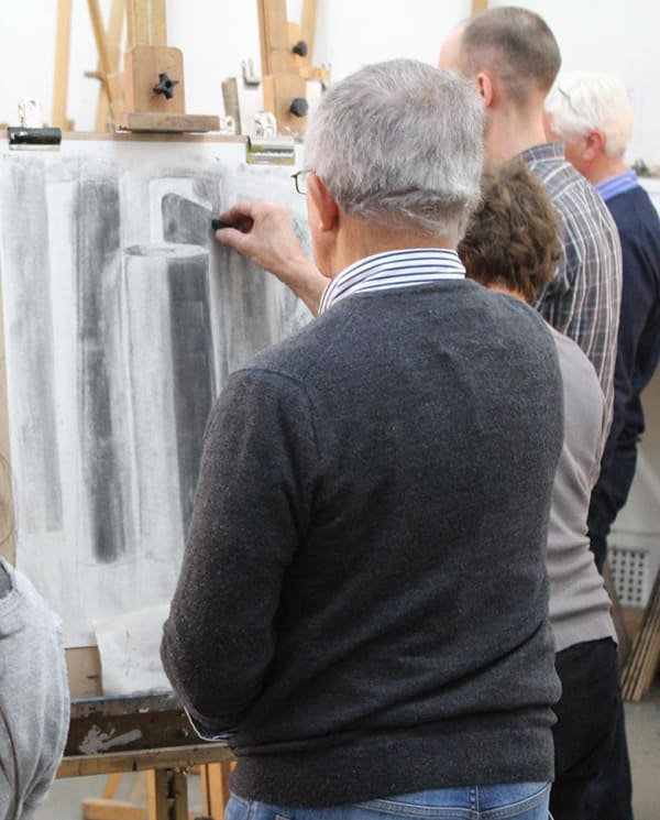 students draw with charcoal at easels