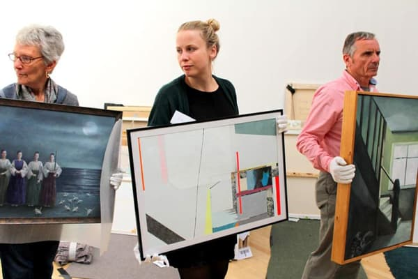 volunteers carry artworks during RWA selection day
