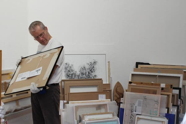 an art technician with stacks of paintings