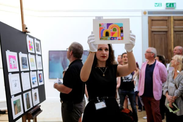 photo of lady holding up postcard during auction