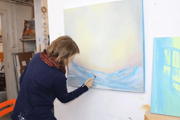photo of jemma grundon painting in her studio