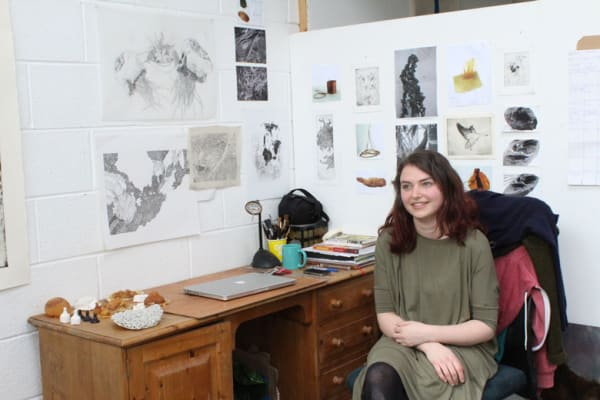 photo of alice freeman sat at a desk in her studio surrounded by work