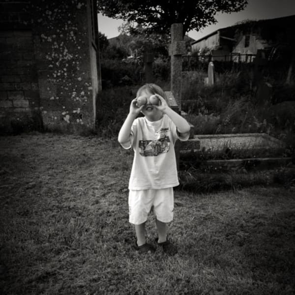 photo by Suze Eyles of a child holding oranges up to its eyes