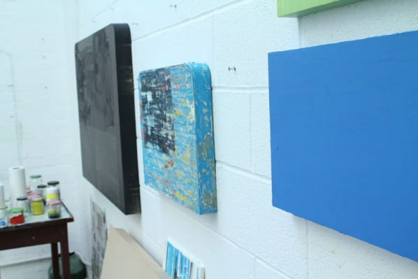 photo of some of Stewart Geddes' paintings on the wall