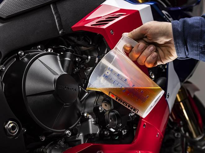 Remplissage d'huile dans une moto avec le verre doseur gradué IPONE