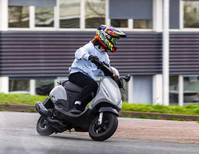 Une personne conduit un scooter 2 temps sur route
