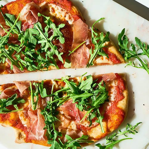 Prosciutto arugula pizza made with Sonoma Gourmet's heirloom tomato pizza sauce and basil parmesan olive oil
