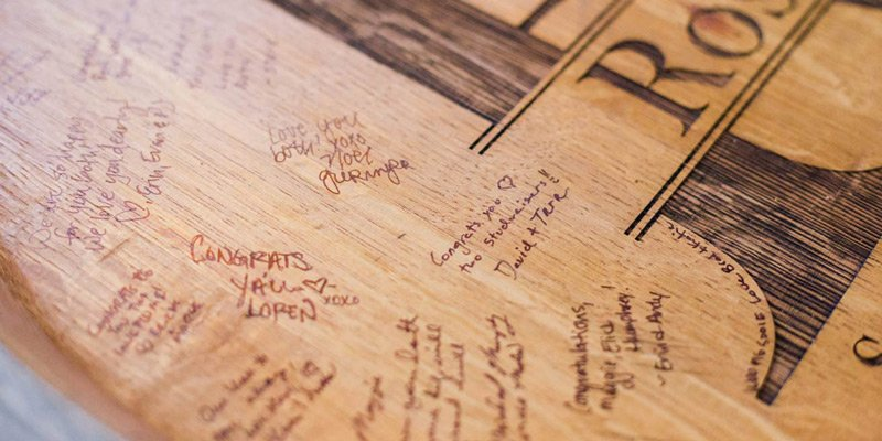 Engraved barrel head guestbook with signatures and messages from wedding guests