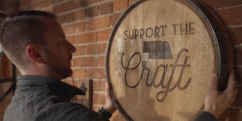 Man hanging on a brick wall a laser engraved barrel head with Support the Craft and state of Nebraska engraved on it.