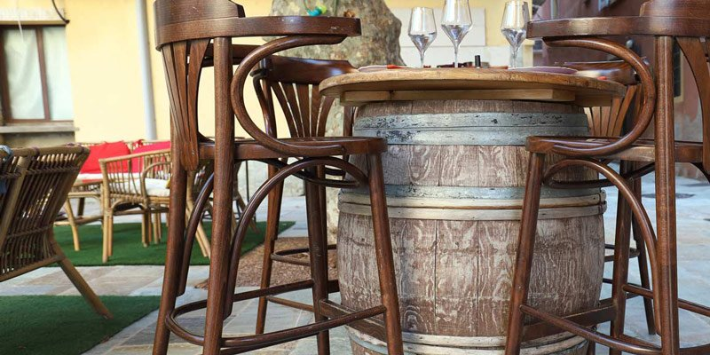 Barrel repurposed as table with wine glasses on top and wooden bar stools around