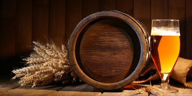 Beer ingredients, barrel and a glass of beer