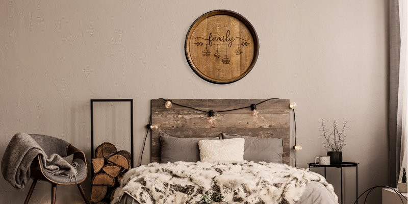 Engraved barrel head hung on wall over a bed with other rustic decor