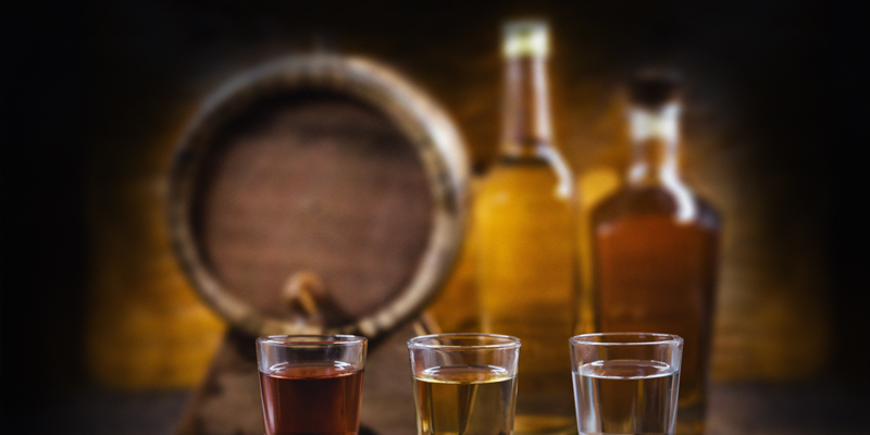 Three full shot glasses in front of aging barrel and bottles of spirits.