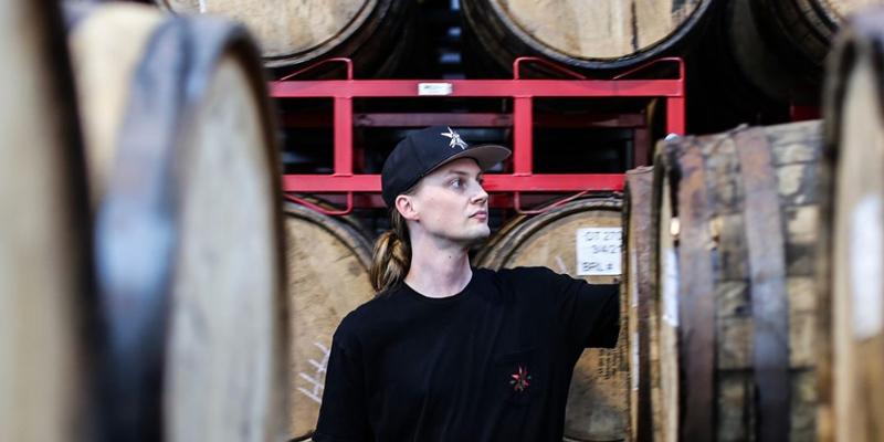 Revolution Brewing's barrel program manager Marty Scott looks at whiskey barrels set on racks and aging beer.