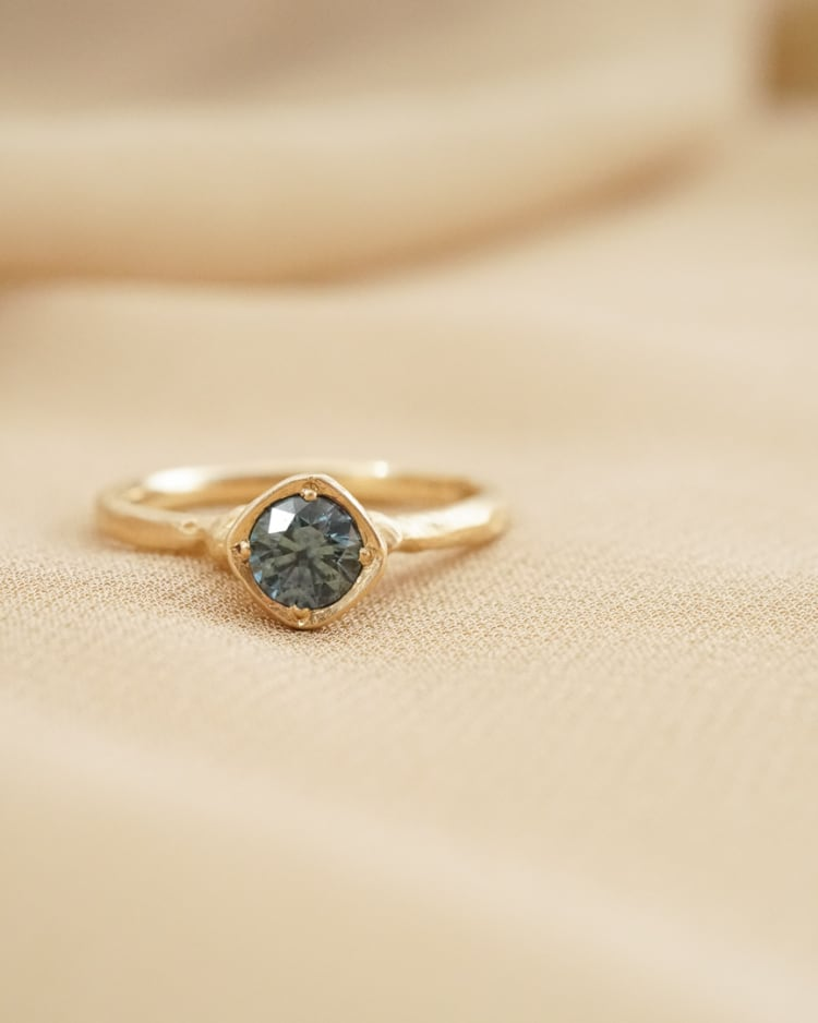 0.5ct Venus Solitaire with Viridian Montana sapphire in 14k recycled gold in a bezel setting with decorative hand carved beads, resting on a tan colored piece of fabric.