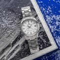 Grand Seiko SBGA211 - titanium wristwatch with a white textured snowflake dial atop a book.
