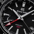Grand Seiko SBGE201 - macro of a black bezel and dial with red accents.