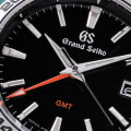 Grand Seiko SBGN003 - macro detail of black dial with red accents.