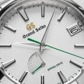 A close up of a light dial wristwatch with a green second hand.