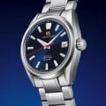 Grand Seiko SLGH003 blue dial stainless steel wristwatch against blue background.