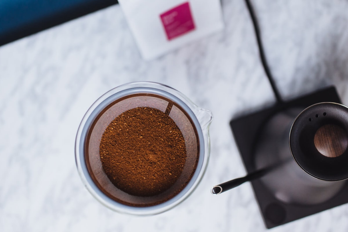 A top down view of the Ratio Kone and glass carafe filled with coffee grounds.